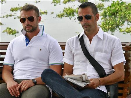 Italian sailors Salvatore Girone (L) and Massimiliano Latorre sit in a private boat after appearing at the police commissioner office in the southern Indian city of Kochi November 14, 2012. REUTERS/Sivaram V