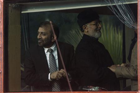 Member of coalition partner of the government and Pakistan's political party Muttahida Qaumi Movement (MQM), Farooq Sattar Sufi (L), is seen behind the window of an armoured vehicle as he meets the cleric and leader of Minhaj-ul-Quran Muhammad Tahirul Qadri (C) on the fourth day of Qadri's protests in Islamabad January 17, 2013. REUTERS/Akhtar Soomro