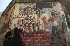 """Unas mujeres egipcias pasan junto a un mural en la plaza Tahrir en El Cairo, ene 16 2013. Los países cuyos líderes fueron derrocados en las revueltas de la """"Primavera Árabe"""" del 2011 tuvieron en su mayoría avances democráticos durante el 2012, pero la turbulencia social generó algunos colapsos en la región, mostró un sondeo anual sobre libertades políticas y civiles alrededor del mundo. REUTERS/Suhaib Salem"""