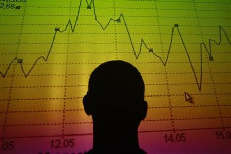 A man is silhouetted in an electronic board showing the FTSE MIB Index for the Italian equity market in this photo illustration taken in Rome August 9, 2011. REUTERS/Tony Gentile