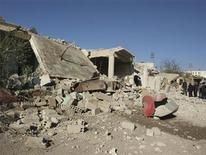 Un grupo de residentes observa una serie de edificios presuntamente dañados por misiles disparados por un jet de la Fuerza Aérea Siria en Daraya, ene 17 2013. Más de 100 personas murieron fusiladas, acuchilladas y posiblemente quemadas en la ciudad siria de Homs esta semana, dijo el jueves un grupo de seguimiento del conflicto, en momentos en que feroces enfrentamientos estallaban en varias partes del país. REUTERS/Kenan Al-Derani/Shaam News Network/Handout Imagen para uso no comercial, ni ventas, ni archivos. Solo para uso editorial. No para su venta en marketing o campañas publicitarias. Esta imagen fue entregada por un tercero y es distribuida, exactamente como fue recibida por Reuters, como un servicio para clientes.