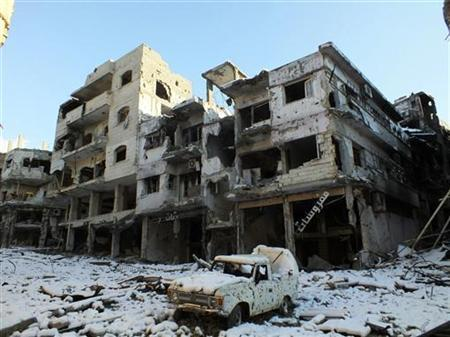 A damaged car and buildings covered with snow are seen at Jouret al Shayah area in Homs January 10, 2013. Picture taken January 10, 2013. REUTERS/Yazan Homsy
