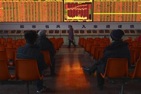Investors sit in front of an electronic board showing stock information at a brokerage house in Taiyuan, Shanxi province, January 14, 2013. REUTERS/Stringer