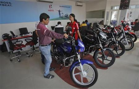 An employee speaks to a customer inside a Hero MotoCorp showroom in Mumbai January 17, 2013. REUTERS/Danish Siddiqui/Files