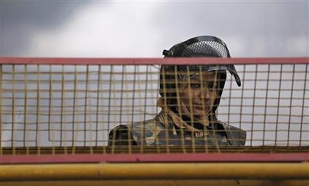 A policewoman stands guard at a barricade to stop protesters, near India Gate in New Delhi December 29, 2012. REUTERS/Adnan Abidi/Files