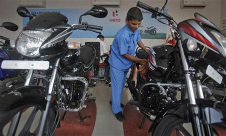 A worker cleans a bike inside a Hero MotoCorp showroom in Mumbai January 17, 2013. REUTERS/Danish Siddiqui/Files