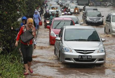 Workers walk through a flooded street as they head to work in the business district in Jakarta January 18, 2013. REUTERS/Beawiharta