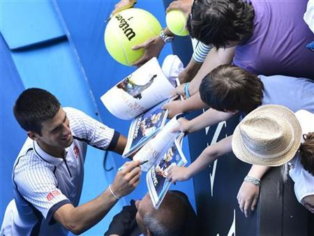 Novak Djokovic of Serbia signs autographs after defeating Radek Stepanek of Czech Republic in their men's singles match at the Australian Open tennis tournament in Melbourne January 18, 2013. REUTERS/Toby Melville