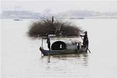 Locals manoeuvre their small vessels along the Mekong river in Phnom Penh November 7, 2012. REUTERS/Samrang Pring