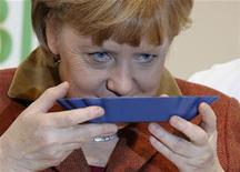 German Chancellor Angela Merkel smells roasted coffee beans at the Internationale Gruene Woche (International Green Week) agriculture and food fair on its opening day in Berlin January 18, 2013. REUTERS/Fabrizio Bensch