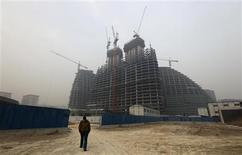 A man walks near a construction site in Beijing January 18, 2013. REUTERS/Jason Lee
