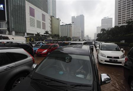 People sit in their cars as they are stranded on a flooded street in the business district in Jakarta January 18, 2013. REUTERS/Beawiharta