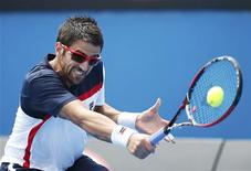 Janko Tipsarevic of Serbia hits a return to Julien Benneteau of France during their men's singles match at the Australian Open tennis tournament in Melbourne, January 18, 2013. REUTERS/Daniel Munoz