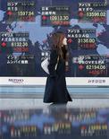 Mulher passa por quadro mostrando índices de ações em frente a uma corretora em Tóquio. O governo e o banco central do Japão concordaram em estabelecer uma nova meta de inflação de 2 por cento na próxima semana, quando a autoridade monetária vai avaliar também fazer um compromisso aberto para comprar ativos até que a meta esteja à vista, disseram à Reuters fontes familiarizadas com o pensamento do BC. 18/01/2013 REUTERS/Kim Kyung-Hoon