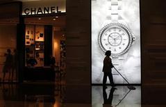 Mulher limpa o chão diante da loja de luxo Chanel em shopping de Xangai, em junho de 2012. O chefe do Departamento Nacional de Estatísticas da China, Ma Jiantang, disse que o regime comunista deveria promover reformas para reduzir as disparidades entre ricos e pobres. 04/06/2012 REUTERS/Carlos Barria