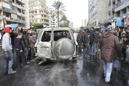 Civilians inspect a burnt car, which is part of Lebanese Minister of Sports and Youth Faisal Karami's convoy, after it was ambushed by gunmen in the northern city of Tripoli January 18, 2013. REUTERS/Omar Ibrahim