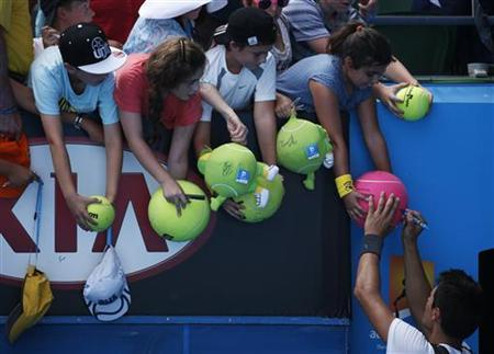 Bernard Tomic of Australia signs autographs for fans after defeating Daniel Brands of Germany in their men's singles match at the Australian Open tennis tournament in Melbourne, January 17, 2013. REUTERS/David Gray