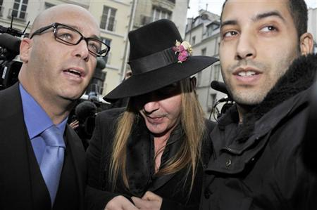 Fashion designer John Galliano (C) and his lawyer Stephane Zerbib (L) arrive for a hearing at a police station in Paris February 28, 2011. REUTERS/Gonzalo Fuentes