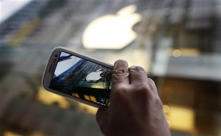 A passerby photographs an Apple store logo with his Samsung Galaxy phone on the morning iPhone 5 went on sale to the public in central Sydney September 21, 2012. REUTERS/Tim Wimborne/Files