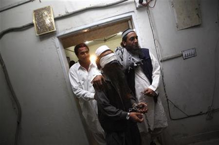Plain clothed police move a handcuffed and blindfolded man through the halls of the Police Crime Investigation Department (CID) after show casing him to media in Karachi on February 17, 2010. REUTERS/Akhtar Soomro/Files