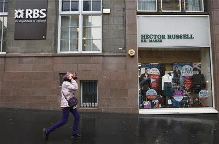 A woman covers her head from the rain as she walks past a Royal Bank of Scotland (RBS) branch in Edinburgh, Scotland November 14, 2012. REUTERS/David Moir/Files