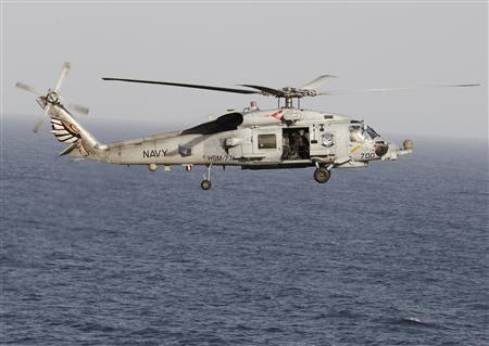 A Sikorsky SH-60 Seahawk helicopter flies near the Nimitz-class aircraft carrier USS Abraham Lincoln (CVN 72) during a transit through the Strait of Hormuz, in this February 14, 2012, file photo. REUTERS/Jumana El Heloueh/Files