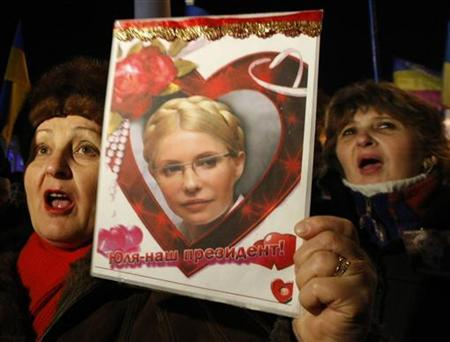 An opposition supporter holds a poster displaying jailed former Prime Minister Yulia Tymoshenko during a rally to mark the eighth anniversary of the Orange Revolution in Kiev November 22, 2012. REUTERS/Anatolii Stepanov