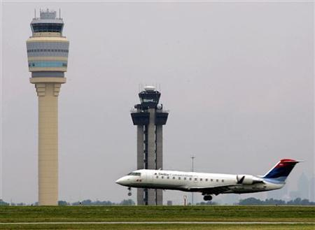 A Delta Air Lines aircraft lands alongside the new FAA air traffic control tower at Hartsfield-Jackson Atlanta International Airport in Atlanta, Georgia May 16, 2006. REUTERS/Tami Chappell