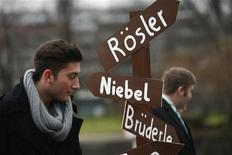 A young liberal from Germany's Free Democratic party (FDP) holds a sign during a protest prior to the traditional FDP epiphany meeting in Stuttgart January 6, 2013. REUTERS/Ralph Orlowski
