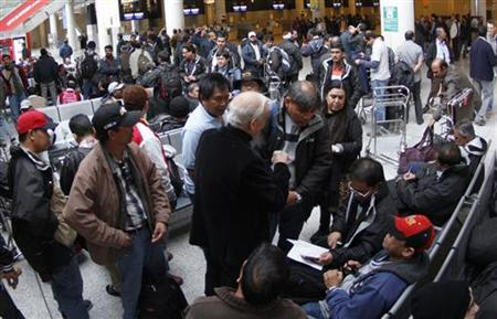 Oil workers from India, Pakistan and Philippines prepare before boarding their flight after arriving to Palma de Mallorca airport at Spanish Balearic island of Mallorca, January 18, 2013. Oil workers evacuated from Algeria following an Al Qaeda linked attack arrived at Palma de Mallorca airport on Thursday night and wait for connecting flights home. REUTERS/Enrique Calvo