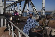 People on donkey-drawn carts cross a strategic bridge over a dam on the Niger River secured by French forces in Markala, Mali January 18, 2013. REUTERS/Joe Penney