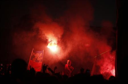 A man holds up a lit flare at Tahrir square in Cairo January 18, 2013, during a protest demanding justice for 74 people killed in a stadium stampede in Port Said last year. REUTERS/Suhaib Salem