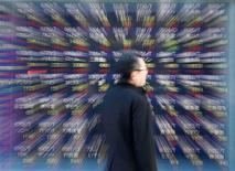 La bolsa española recogió beneficios el viernes por recogida de beneficios tras la reciente racha alcista, aunque el fondo de mercado seguía siendo positivo tras datos económicos chinos que alentaban el optimismo sobre la economía global. En la imagen, un hombre mira una pantalla con índices bursátiles en una correduría de Tokio, el 18 de enero de 2013. REUTERS/Kim Kyung-Hoon