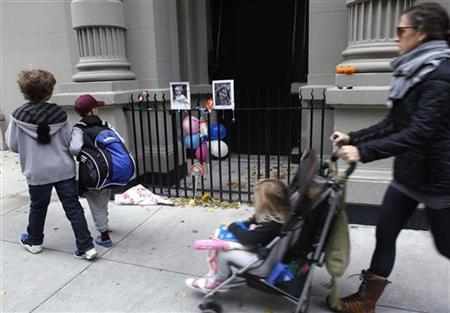 A family walks past a makeshift memorial left outside the Krim family apartment in New York, October 28, 2012. REUTERS/Carlo Allegri