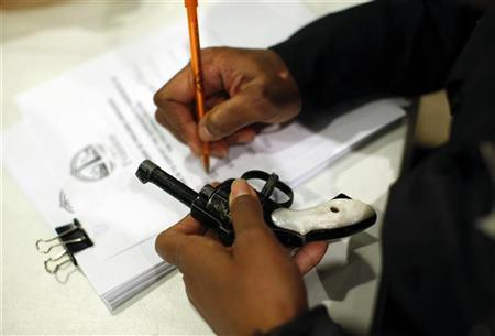 An Evanston police officer documents some information on a firearm that was turned in as part of an amnesty-based gun buyback program in Evanston, Illinois December 15, 2012. REUTERS/Jim Young