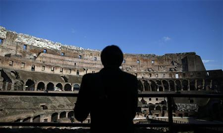 A tourist is silhouetted as he visits Rome's ancient Colosseum January 18, 2013. REUTERS/Tony Gentile