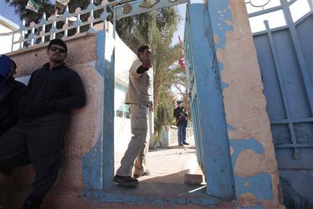 An Algerian guard gestures at the main entrance of a hospital in In Amenas, as people wait to know the fate of their relatives who were taken hostage by Islamist militants in a gas facility, January 18, 2013. REUTERS/Ramzi Boudina