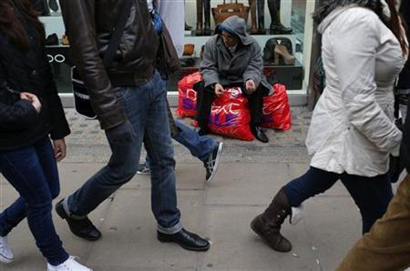 A shopper rests on his sale bags as others walk past him on Oxford Street in central London, December 26, 2012. REUTERS/Andrew Winning