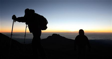 Climbers walk up the steep gravel and scree slope leading to the summit of Mount Kilimanjaro, one of the world