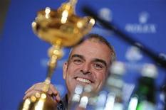 Paul McGinley of Ireland smiles near the Ryder Cup during a news conference after being named the European Ryder Cup captain at the St. Regis in Saadiyat Islands in Abu Dhabi January 15, 2013. McGinley was the unanimous choice of the Players Committee at a meeting in Abu Dhabi and becomes Ireland's first skipper in the history of the event launched in 1927. REUTERS/Ben Job
