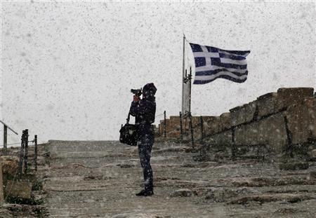 A tourist takes photos during a snowstorm atop Athens' Acropolis January 8, 2013. REUTERS/Yannis Behrakis
