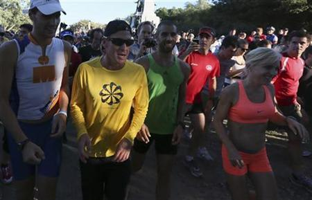 Lance Armstrong (2nd L) runs with with a crowd of people after sending a tweet to Montrealers to meet him for a run at Mount Royal park in Montreal August 29, 2012. REUTERS/Christinne Muschi/Files