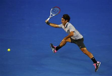 Roger Federer of Switzerland hits a return to Bernard Tomic of Australia during their men's singles match at the Australian Open tennis tournament in Melbourne January 19, 2013. REUTERS/David Gray