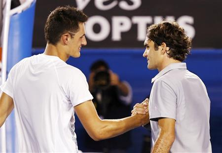 Roger Federer of Switzerland (R) shakes hands with Bernard Tomic of Australia after defeating him in their men's singles match at the Australian Open tennis tournament in Melbourne January 19, 2013. REUTERS/Daniel Munoz