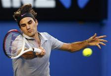 Roger Federer of Switzerland hits a return to Bernard Tomic of Australia during their men's singles match at the Australian Open tennis tournament in Melbourne January 19, 2013. REUTERS/Daniel Munoz