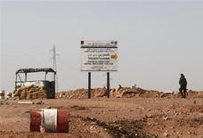 Militaire algérien à un point de contrôle à environ 10 kilomètres du complexe gazier algérien de Tiguentourine, près d'In Amenas, dans l'est de l'Algérie. Seize otages étrangers, dont deux Américains, deux Allemands et un Portugais, ont été libérés samedi sur ce site, selon une source informée. /Photo prise le 19 janvier 2013/REUTERS/Ramzi Boudina