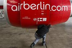 An Air Berlin technician opens the cover of a jet engine of an Air Berlin plane at a hangar at Tegel Airport in Berlin, January 16, 2013. German airline Air Berlin , part-owned by Abu Dhabi-based carrier Etihad, plans to cut almost 10 percent of its workforce of 9,300 as part of a cost-cutting campaign aimed at halting years of losses. REUTERS/Thomas Peter (GERMANY - Tags: TRANSPORT BUSINESS)
