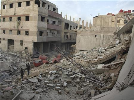 Residents stand near buildings damaged by what activists said were missiles fired by a Syrian Air Force fighter jet loyal to President Bashar al-Assad in Daraya January 18, 2013, in this picture provided by Shaam News Network. REUTERS/Kenan Al-Derani/Shaam News Network/Handout