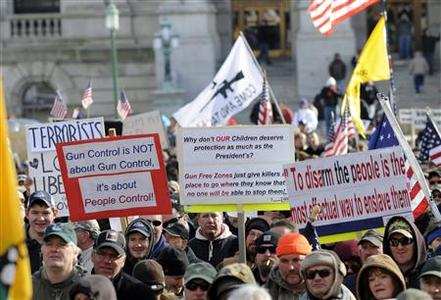 People hold protest signs during the Guns Across America pro-gun rally at the State Capitol in Albany, New York, January 19, 2013. REUTERS/Hans Pennink