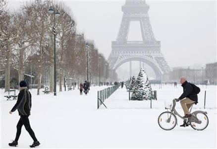 A man rides a Velib self-service public bicycle as he makes his way along a snow-covered area at the Champs de Mars near the Eiffel Tower in Paris January 19, 2013. REUTERS/John Schults